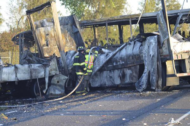 Firefighters hose down the wreckage of a bus and a semitruck that collided Thursday just north of Orland, Calif., that left 10 dead. Authorities say a FedEx truck crossed a grassy median on the hi ...