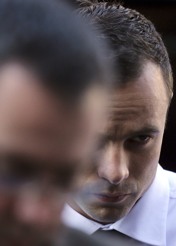 Oscar Pistorius arrives at the high court in Pretoria, South Africa, Friday, April 11, 2014. The chief prosecutor laughed scornfully at an answer from Pistorius during the Olympic athlete's murder ...