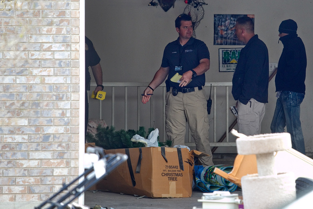 Authorities investigate a crime scene at a house in Pleasant Grove, Utah, Sunday, April 13, 2014. According to the Pleasant Grove Police Department, seven dead infants were found in the former hom ...