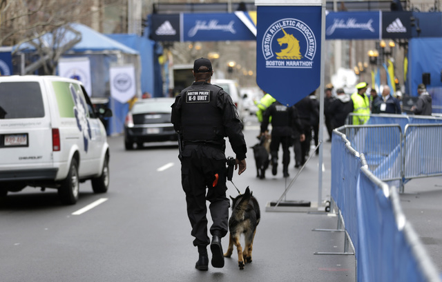 A law enforcement official patrols the area with a dog near the finish line of the Boston Marathon, Tuesday, April 15, 2014, in Boston. (AP Photo/Steven Senne)