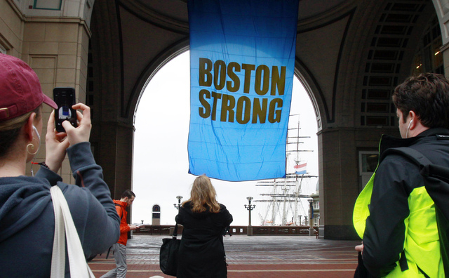 """People photograph a banner reading """"Boston Strong"""" as it hangs at Rowes Wharf on the first anniversary of the Boston Marathon bombings, Tuesday, April 15, 2014, in Boston. (AP Photo/Bill ..."""