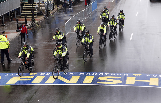 Police on bikes cycle across the Boston Marathon finish line prior to a remembrance ceremony for family members and survivors of the 2013 Boston Marathon bombing on Boylston Street in Boston, Tues ...