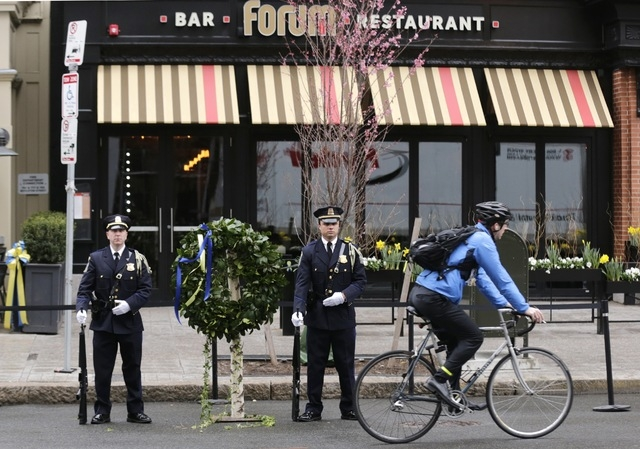 A Boston Police honor guard is posted outside the Forum restaurant, the site of the second of two bombs that exploded near the finish line of the 2013 Boston Marathon, Tuesday, April 15, 2014 in B ...