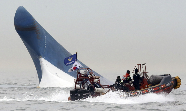 South Korean coast guard officers try to rescue passengers from a ferry sinking in the water off the southern coast near Jindo, south of Seoul, South Korea, Wednesday, April 16, 2014. The ferry ca ...