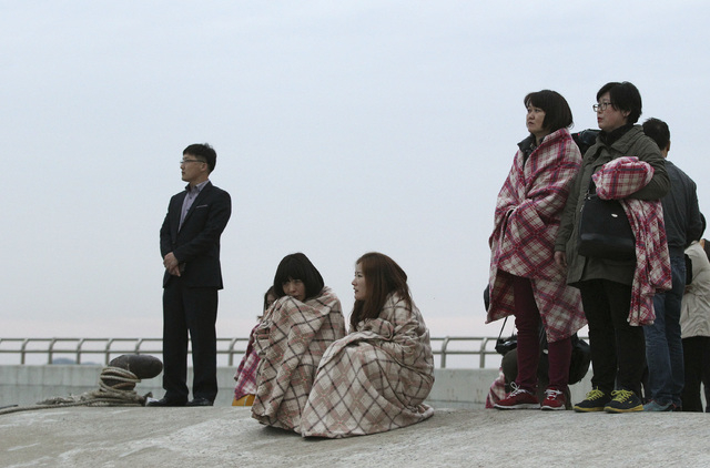 Relatives wait for their missing loved ones at a port in Jindo, South Korea, Wednesday, April 16, 2014. A ferry carrying 459 people, mostly high school students on an overnight trip to a tourist i ...