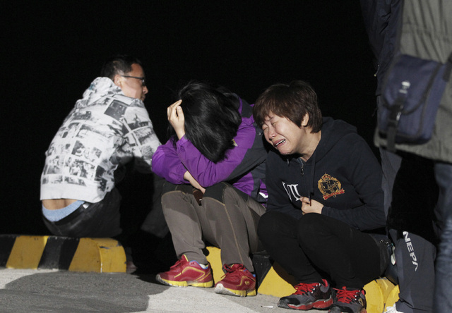 A relative weeps as she waits for missing passengers of a sunken ferry at Jindo port, South Korea, Wednesday, April 16, 2014. The ferry carrying 459 people, mostly high school students on an overn ...