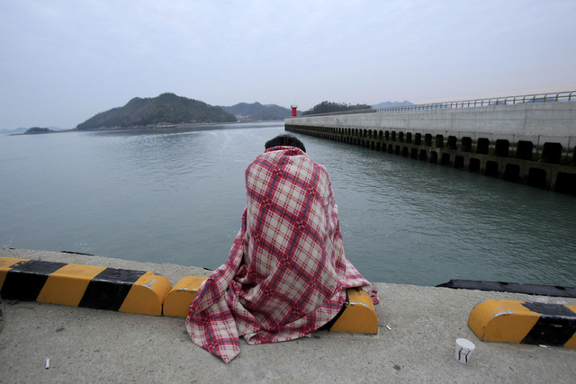 A relative waits for their missing loved one at a port in Jindo, South Korea, Wednesday, April 16, 2014. A ferry carrying 459 people, mostly high school students on an overnight trip to a tourist  ...