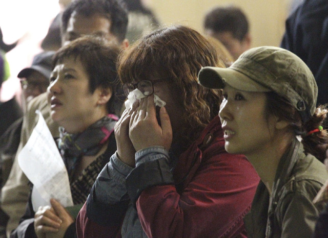 A mother weeps as she and others search for their children's names among a list of survivors rescued from a ferry that sank off the country's southern coast, at Danwon high school in Ansan, South  ...