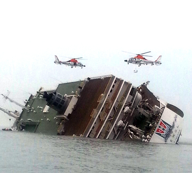South Korean rescue helicopters fly over a South Korean passenger ship, trying to rescue passengers from the ship in water off the southern coast in South Korea, Wednesday, April 16, 2014. The Sou ...