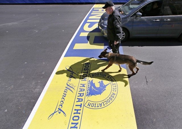Boston Police officer John Quinn walks with Miller, his bomb detection canine, over the finish line while sweeping the area in preparation for the Boston Marathon, Wednesday, April 16, 2014, in Bo ...
