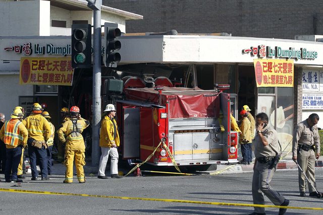 Firefighters and other officials work the scene of an accident where two firetrucks answering a call collided en route to a fire Wednesday, April 16, 2014, in Monterrey Park, Calif. The collision  ...