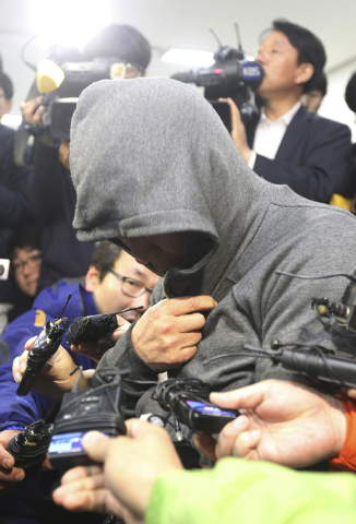 Lee Joon-seok, the captain of a sunken ferry in the water off the southern coast arrives to be investigated at Mokpo Police Station in Mokpo, South Korea, Thursday, April 17, 2014. An immediate ev ...