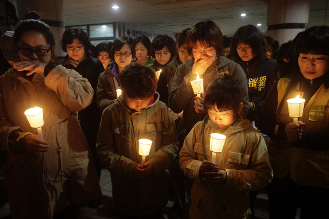 People gather to pray with candlelights for the missing passengers of a sunken ferry at Danwon High School in Ansan, South Korea, Thursday, April 17, 2014. An immediate evacuation order was not is ...