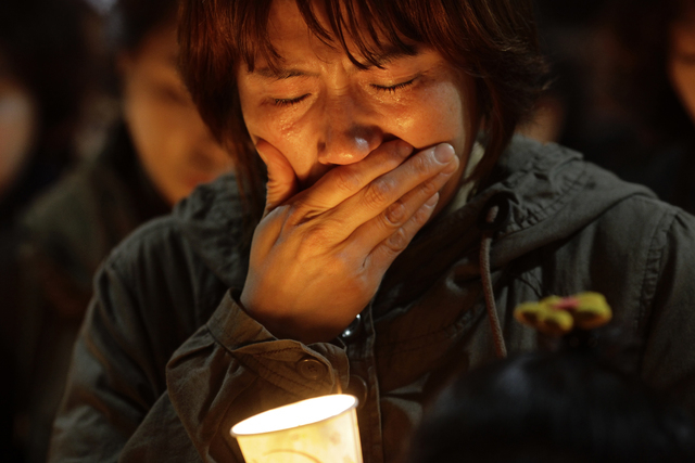 A woman offers prayer with candlelight for the missing passengers of a sunken ferry at Danwon High School in Ansan, South Korea, Thursday, April 17, 2014. An immediate evacuation order was not iss ...