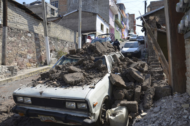 A parked car suffered damage when a adobe wall collapsed on it after a strong earthquake shook Chilpancingo, Mexico, Friday, April 18, 2014. A powerful magnitude-7.2 earthquake shook central and s ...