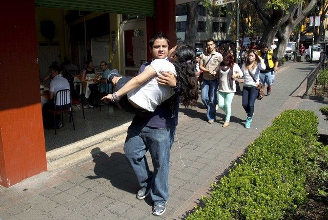 A woman is carried at the Juarez neighborhood after a strong earthquake jolted Mexico City, Friday, April 18, 2014. The powerful magnitude-7.2 earthquake shook central and southern Mexico but ther ...