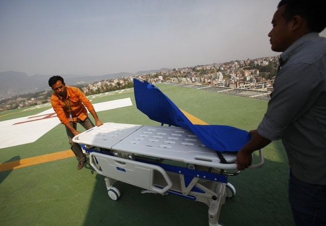 Hospital staff get ready to receive the injured from an avalanche on helipad of Grandy hospital, in Katmandu, Nepal, Friday, April 18, 2014. An avalanche swept down a climbing route on Mount Evere ...