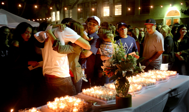 "Trish Arzola, the mother of Arthur ""Tury"" Arzola, Jr. is hugged by her sons David and James at a candlelight vigil, as family, friends and colleagues gathered for a memorial service on Wed. April  ..."