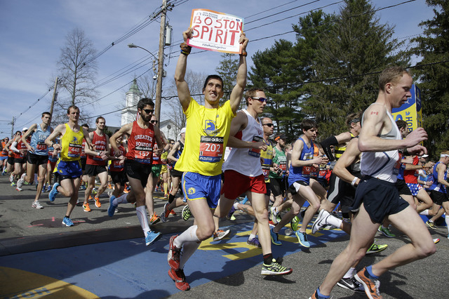 Runners in the first wave of 9,000 cross the start line of the 118th Boston Marathon Monday, April 21, 2014 in Hopkinton, Mass.  (AP Photo/Stephan Savoia)