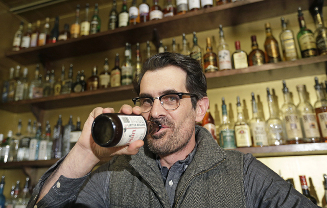 In this April 16, 2014 photo, actor Ty Burrell, who plays bumbling dad Phil Dunphy on ABC's Modern Family, drinks a beer at Bar X, the cocktail bar he co-owns, in Salt Lake City. Burrell just open ...