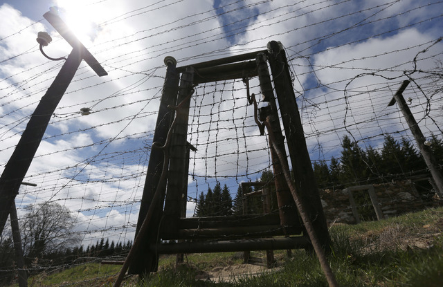 Near the village of Kvilda, Czech Republic, on Wednesday, April 9, 2014 the reconstruction of Iron Curtain stands in the Sumava National Park. The Iron Curtain was traced by a real electrified bar ...