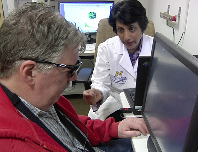 In this April 16, 2014 image from video Dr. Naheed Khan, right, works with Roger Pontz, left, on an exercise to test how well he sees shapes on a computer screen at the University of Michigan Kell ...
