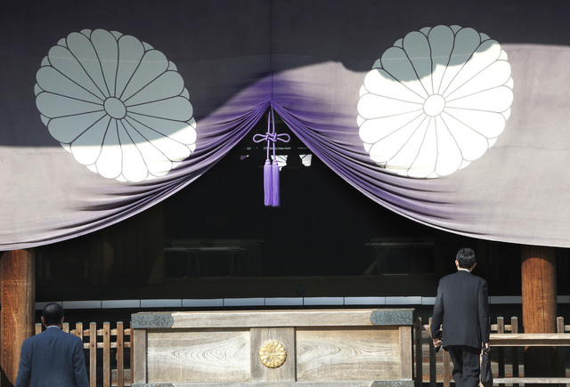 A group of Japanese lawmakers, seen silhouetted in the middle of the photo, offer prayers at the Yasukuni Shrine, which honors Japan's war dead, including World War II leaders convicted of war cri ...