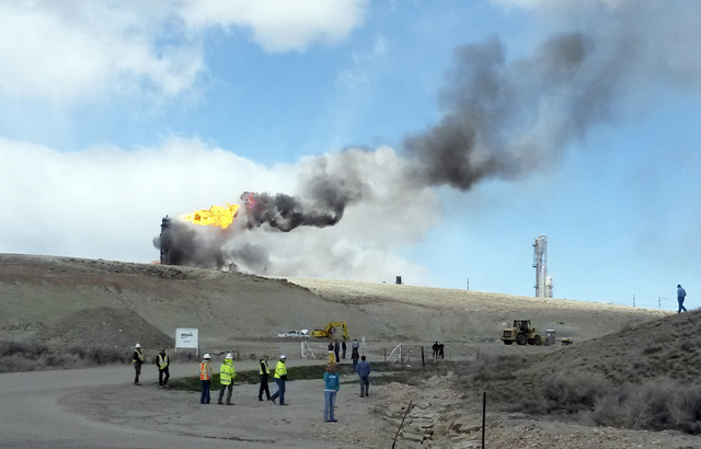 This image provided by Rachel Anderson shows officials at the site of an explosion and fire at a natural gas processing facility and major national pipeline hub, Wednesday, April 23, 2014, in Opal ...
