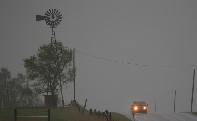 A vehicle tops a hill along U.S. Route 56 as a severe thunderstorm moves through the area near Baldwin City, Kan., Sunday, April 27, 2014. Severe storms are expected in the area most of the day. ( ...