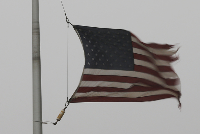 A flag is tattered in the wind of a severe thunderstorm at a farm credit office near Baldwin City, Kan., Sunday, April 27, 2014. Severe storms are expected in the area most of the day. (AP Photo/O ...