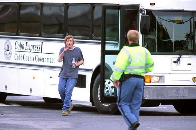 FedEx employee David Chumley talks to a Cobb County Police officer after he was bused out of the blocked off area after an early morning workplace shooting at the Airport Road FedEx facility Tuesd ...