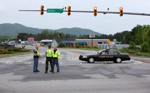 Cobb County Police block off Old US 41 Highway after an early morning workplace shooting at the Airport Road FedEx facility Tuesday April 29, 2014, in Kennesaw, Ga. A shooter opened fire at a FedE ...