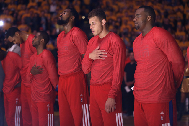 Los Angeles Clippers players listen to the national anthem wearing their warmup jerseys inside out to protest alleged racial remarks by team owner Donald Sterling before Game 4 of an opening-round ...