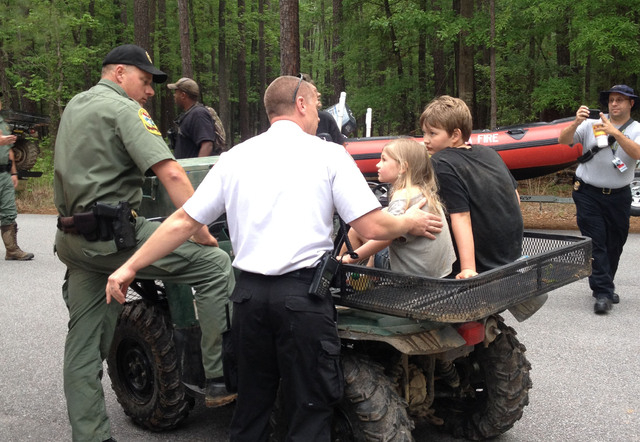 This photo provided by the National Park Service, rescue personnel attend to Dakota Kimbler, 10 and his sister Jade Kimbler, 6, after they were lost with their father inside Congaree National Park ...