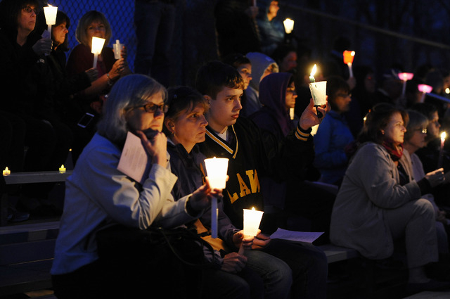 People raise candles as they listen to Maren Sanchez sing during a vigil for her at Jonathan Law High School, Monday, April 28, 2014, in Milford, Conn. Sanchez was fatally stabbed inside the schoo ...