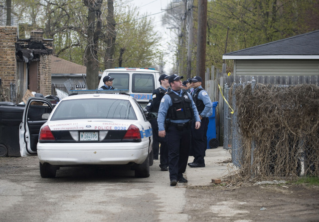 In this Monday, April 28, 2014 photo, police stand outside a residence in Chicago after 14-year-old girl was fatally shot and another girl wounded in the Back of the Yards neighborhood in Chicago. ...