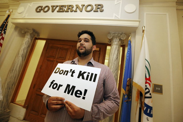 Hossein Dabiri with Oklahoma Coalition Against the Death Penalty holds a sign protesting the death penalty at the State Capitol in Oklahoma City, Tuesday April 29, 2014. Oklahoma prison officials  ...