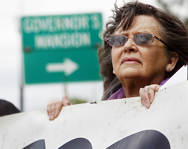 Fannie Bates of Oklahoma City holds a sign urging Gov. Mary Fallin to issue a stay in the execution of two inmates, during a protest Tuesday, April 29, 2014, near the Governor's Mansion in Oklahom ...