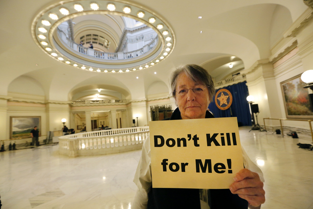 Margaret Cox with Oklahoma Coalition Against the Death Penalty holds a sign protesting the death penalty at the State Capitol in Oklahoma City, Tuesday April 29, 2014. Oklahoma prison officials ha ...