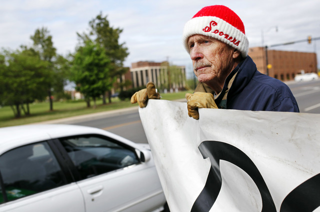 Protester John Walters of Oklahoma City holds a sign urging Gov. Mary Fallin to issue a stay in the execution of two inmates, near the Governor's Mansion in Oklahoma City on Tuesday, April 29, 201 ...