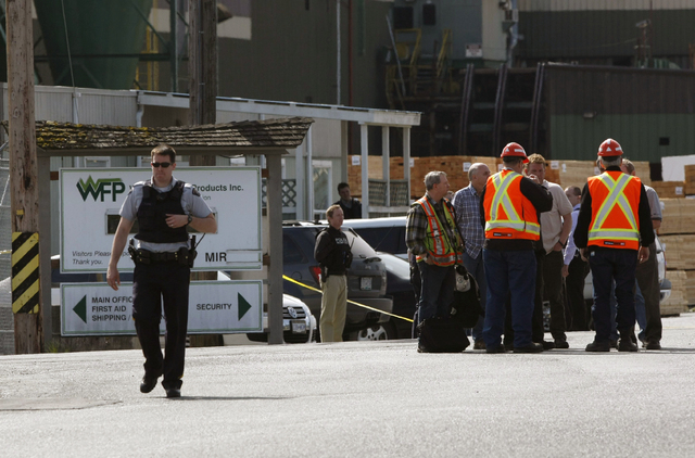 Mill workers talk as a police officer walks away following a shooting at Western Forest Products in Nanaimo, British Columbia, Wednesday, April 30, 2014. Four people were shot Wednesday at the lum ...