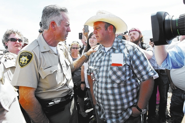 Dave Bundy, right, son of rancher Cliven Bundy, talks with a Metro Police officer while trying to get the BLM to release his cattle from their impound corral near Bunkerville on April 12, 2014. (J ...