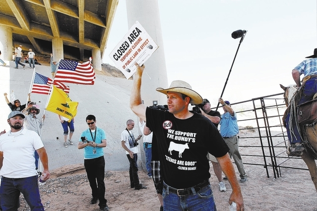 """Ammon Bundy, middle, son of rancher Cliven Bundy, removes a """"closed area"""" sign from the BLM impound corral after the BLM agreed to release his family's a cattle near Bunkerville on April ..."""