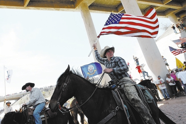 Arden Bundy, son of rancher Cliven Bundy, flies the American flag under the I-15 highway near Bunkerville after the BLM agreed to release his family's cattle on April 12, 2014. (Jason Bean/Las Veg ...