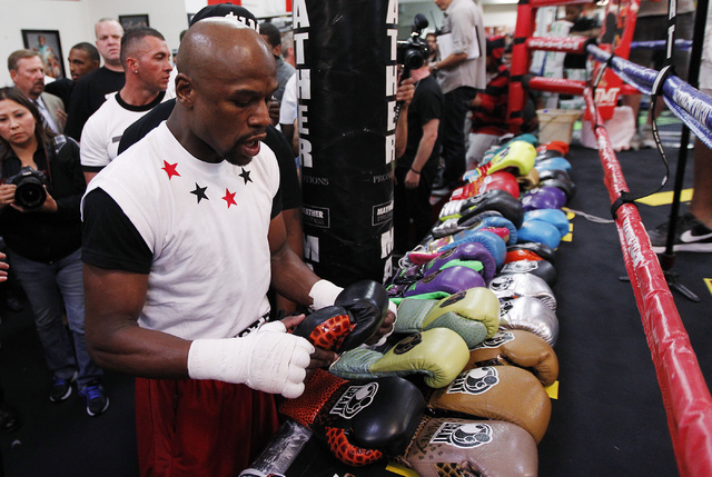 Boxer Floyd Mayweather Jr. picks out some gloves before working out in front of the media in preparation for his upcoming fight against Marcos Maidana at his gym in Las Vegas on April 22, 2014. (J ...