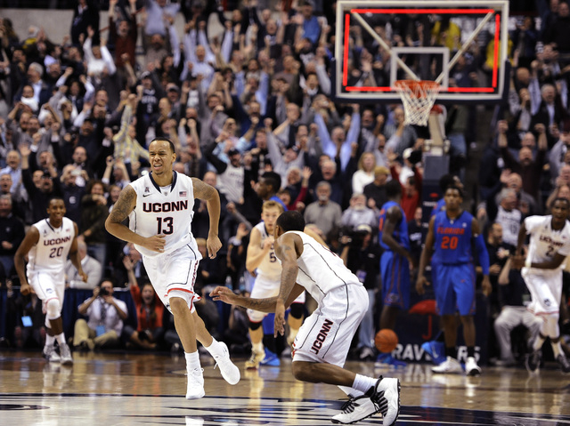 Connecticut's Shabazz Napier, left, and Ryan Boatright, right, react after Napier hits the game winning basket at the end an NCAA college basketball game against Florida, Monday, Dec. 2, 2013, in  ...