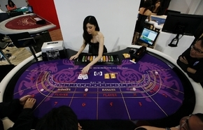 An attendant demonstrates the game of baccarat on a baccarat gaming table during the Global Gaming Expo Asia in Macau on May 23. Almost all of Macau''s $38 billion in gambling revenue last year - ...