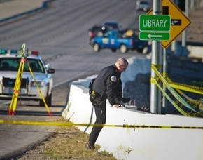 A Henderson police officer leaps over a barrier at St. Rose Parkway and Jeffrey's Street in Henderson, Wednesday, Nov. 11, 2012 while investigating an officer involved shooting. (File, Las Vegas  ...