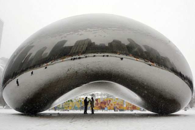A couple check out their reflections on the underside of the 110-ton stainless steel Anish Kapoor sculpture called 'Cloud Gate' and nicknamed 'The Bean' at Millennium Park, in Chicago.  (AP File P ...