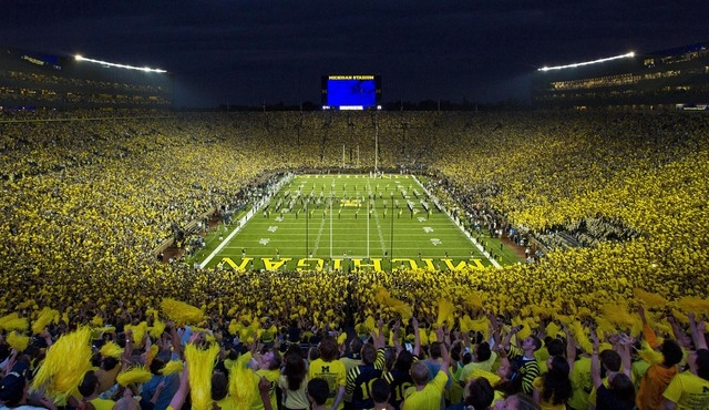 Michigan fans wave pom-poms before a football game in Ann Arbor, Mich. (AP File Photo/Tony Ding)